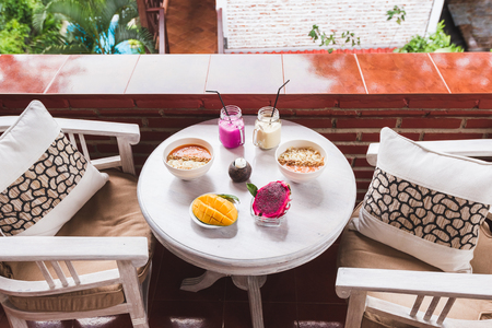 Healthy tropical breakfast on outdoor terrace at home. White vintage round table served with cutted mango and dragon fruit, fresh papaya smoothie and cold shake drinks in bottles
