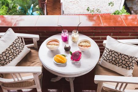 Pequeno-almoço tropical saudável no terraço ao ar livre em casa. Mesa redonda branca vintage servida com frutas de manga e dragão cortadas, smoothie de mamão fresco e bebidas com agitação fria em garrafas Banco de Imagens