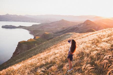 어린 소녀 자연에서 산책 하 고 즐기는 해안, 깃털 잔디 및 석양의 필드보기. 흰색 파란색 셔츠와 긴 머리 색깔의 자물쇠 스톡 콘텐츠