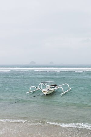 nusa: Two traditional Bali fishing boats on big waves in storm and raining. Candidasa beach