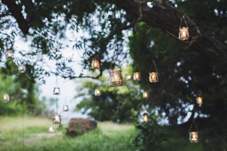 Ceremonia de la boda de noche con un montón de lámparas vintage y velas en el árbol grande Foto de archivo - 81792024