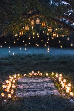 Ceremonia de la boda de noche con un montón de lámparas vintage y velas en el árbol grande Foto de archivo - 81791879