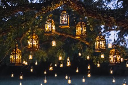 Nachtwedstrijd met veel vintage lampen en kaarsen op grote boom