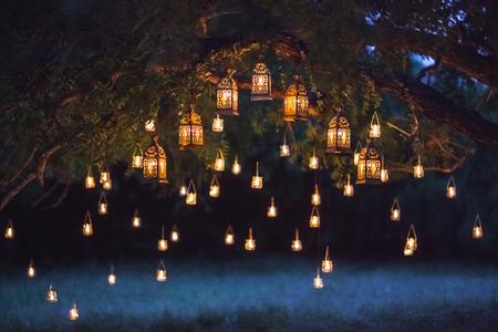 Ceremonia de la boda de noche con un montón de lámparas vintage y velas en el árbol grande Foto de archivo - 81791922