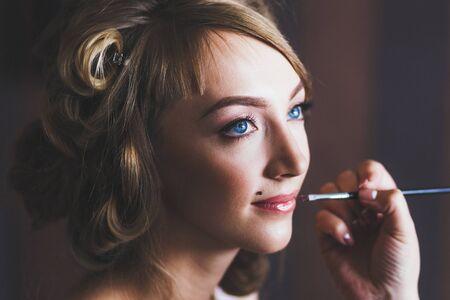 Wedding make-up. Bride lipstick, hand with brush