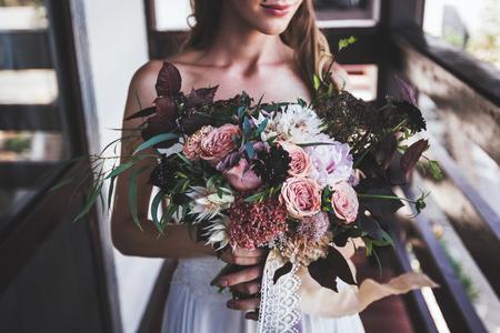 花嫁の手の中の豪華なブーケ。暗い色調で素朴なスタイル