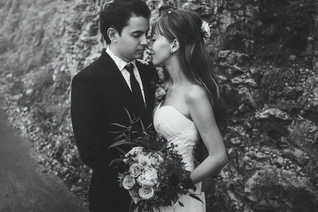 tenderly: Newlyweds tenderly kissing close-up. Black and white toning portrait Stock Photo
