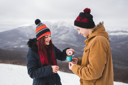 tea hot drink: Couple drink hot tea from thermos at winter. Mountains in snow at background Stock Photo