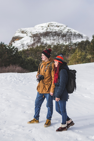 Tourist couple taking photos in mountains with background of snow-capped peak Stock Photo