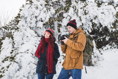 Couple tourists in winter forest. Casual style, beige parka, jeans, red scarf. Taking photo of landscape