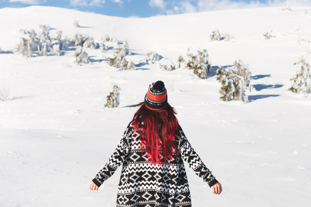 Woman with red hair in knitted cardigan and hat with bubo. Winter portrait in snowy mountains, photo from back