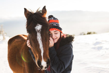 Happy girl gently stroking horse in shiny sunlight. Winter in mountains