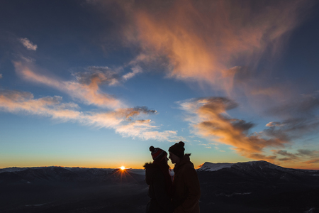 Silhouette of loving couple on background of amazing colorful sunset in mountains. Sun rays on horizon