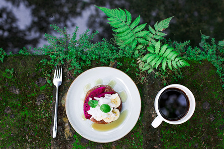 Tasty breakfast outside in garden. Fresh honey wholegrain pancakes with sliced dragon fruit, banana, coconut and mint. Cup of black Bali coffee