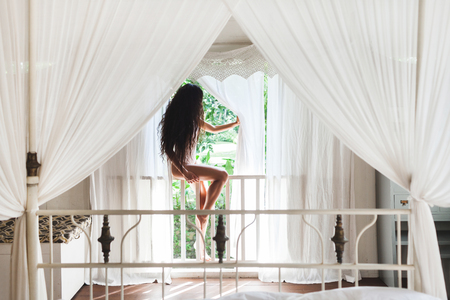 Beautiful woman in white lingerie with long black hair sitting on veranda in front of window with white curtains. Sunlight in room, morning mood Reklamní fotografie