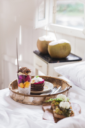 Fresh tasty breakfast in bed on wooden tray. Yogurt with fruits and chia, honey pancakes, two toasts with avocado and poached eggs and two young coconut. White vintage interior Stock Photo