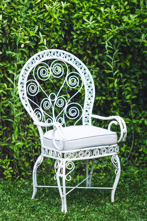 old vintage furniture in garden with natural green background white metal chair and table