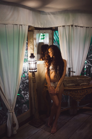 Beautiful sexy girl in white lingerie enjoying in amazing bathroom in Bali style. Handmade carving wooden furniture and lantern light