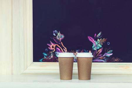 Due bicchieri di carta di cartone con tappo al bancone con motivo autunnale