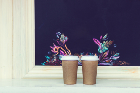 Two carton paper cups with cap at the bar with autumn pattern