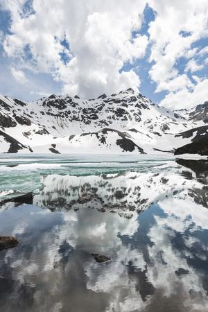 Lago Syltrankel nella regione di Elbrus, Russia. Paesaggio montano invernale panoramico, cime di neve e lago ghiacciato, bella riflessione nell'acqua