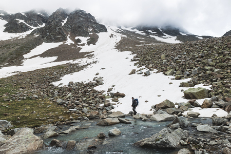 Man hiking in Caucasus mountains in spring, Elbrus Region in Russia. Snowy peaks and cloudy weather, dramatic landscape, panoramic view