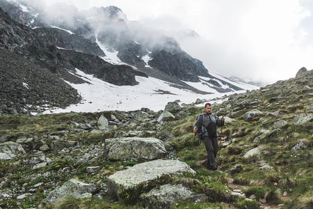 Mężczyzna wycieczkuje w Kaukaz górach w wiośnie, Elbrus region w Rosja. Śnieżne szczyty i pochmurna pogoda, dramatyczny krajobraz, panoramiczny widok