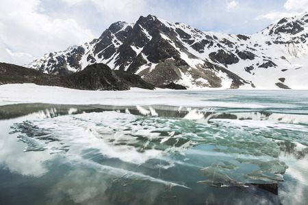 Lake Syltrankel in the Elbrus region, Russia. Panoramic winter mountain landscape, snow peaks and frozen lake, beautiful reflection in the water