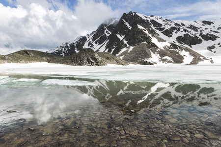 Jeziorny Syltrankel w Elbrus regionie, Rosja. Panoramiczny zimowy krajobraz górski, szczyty śniegu i zamarznięte jezioro, piękne odbicie w wodzie