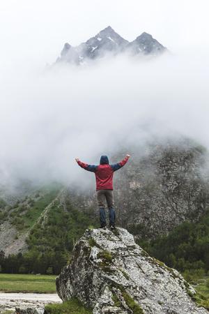 Um homem caminhando para o pico da montanha. Vista dramática com névoa no frio do tempo da manhã. Região de Elbrus