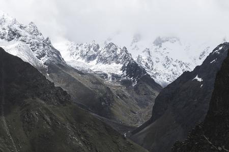 Śnieżni halni szczyty Kaukaz góry w zimnej chmurnej pogodzie, Elbrus region. Główny grzbiet kaukaski