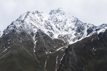 Neve montanhas de montanhas do Cáucaso em clima frio e nublado, região de Elbrus. Cume caucasiano principal