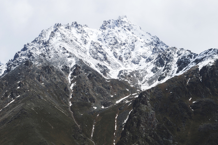 Snow mountain peaks of Caucasus mountains in cold cloudy weather, Elbrus Region. Main caucasian ridge 스톡 콘텐츠