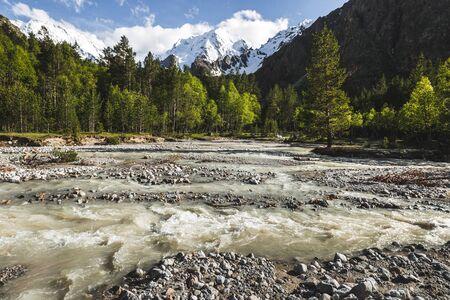 Fluxo forte do rio em montanhas caucasianas, floresta de coníferas e tops de rochas na neve, vista de Ullu-Tau no fundo