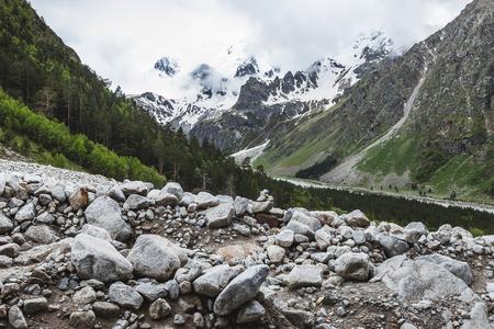Elbrus 地域曇り寒さでコーカサス山脈の山頂は雪です。フォア グラウンドで巨大な石