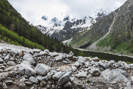 Snow mountain peaks of Caucasus mountains in cold cloudy weather, Elbrus Region. Huge stones on foreground