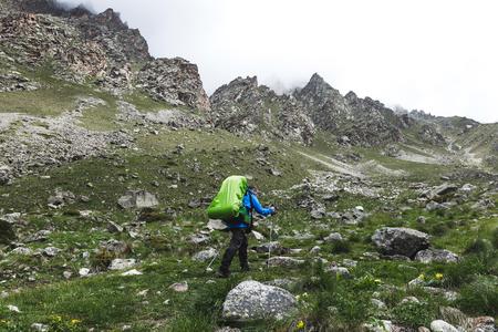大型バックパック高岩と美しい自然周辺の山々 でのハイキングと観光。雪の山のトップ 写真素材