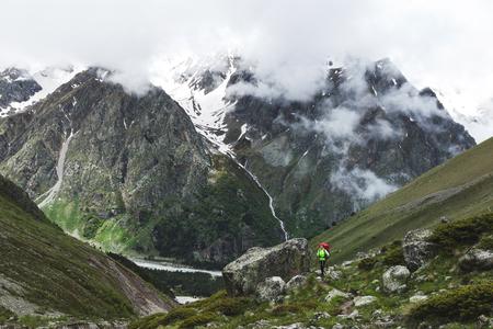 Turista com grande mochila caminhando nas montanhas, em torno de rochas altas e natureza bonita. Montanha na neve