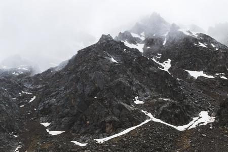Paesaggio montuoso con rocce e nebbia strisciante. Alte cime nelle nuvole, freddo. Turismo in montagna