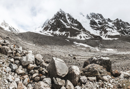 Mountain landscape with rocks and creeping fog. High snow peaks in the clouds, cold weather. Huge stones on foreground Archivio Fotografico