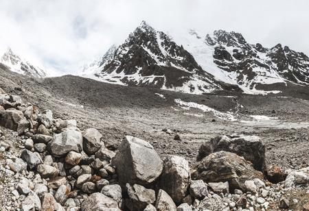 Paesaggio montuoso con rocce e nebbia strisciante. Alte cime di neve nelle nuvole, tempo freddo. Pietre enormi in primo piano Archivio Fotografico