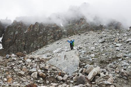 Un uomo che sale sulla cima della montagna. Vista drammatica con nebbia in tempo freddo mattina. Regione di Elbrus