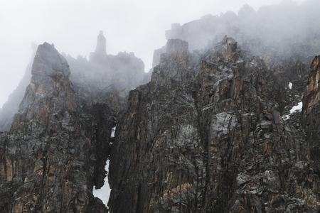 Górski krajobraz ze skał i pnący mgła. Wysokie szczyty w chmurach, zimna pogoda. Turystyka w górach