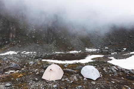 Ð amortecedor com tendas altas nas montanhas no inverno. Nevoeiro, neve e clima frio. Cordilheira e rochas no fundo