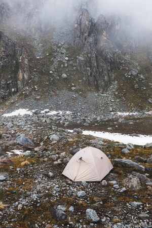 Сamping with tents high in the mountains in winter. Fog, snow and cold weather. Mountain range and rocks on background