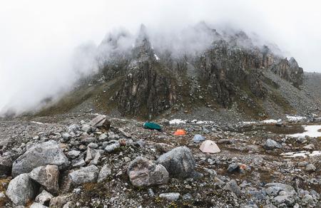 Ð ¡campeggiare con tende in alta montagna in inverno. Nebbia, neve e freddo. Catena montuosa e rocce sullo sfondo. Colpo panoramico Archivio Fotografico