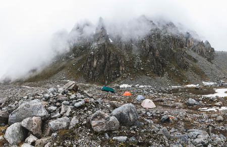 Сamping with tents high in the mountains in winter. Fog, snow and cold weather. Mountain range and rocks on background. Panoramic shot 스톡 콘텐츠