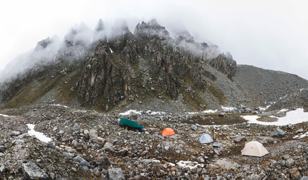 Ð¡amping with tents high in the mountains in winter. Fog, snow and cold weather. Mountain range and rocks on background. Panoramic shot 스톡 콘텐츠