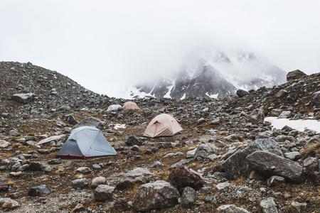 冬の山でテントが高い Сamping。霧、雪および寒い気候。山の範囲と背景の岩