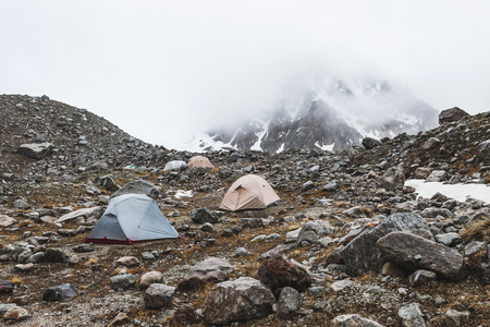 Campeggio con tende alte in montagna in inverno. Nebbia, neve e tempo freddo. Catena montuosa e rocce sullo sfondo